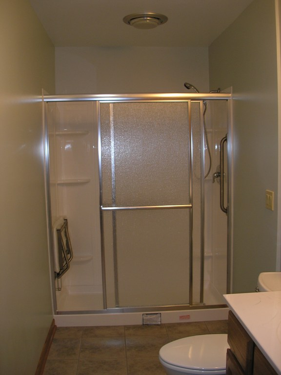 Remodeled bathroom after the removal of the dividing wall, replacement of the bathtub with a low threshold shower, and the installation of certain aging-in-place features.